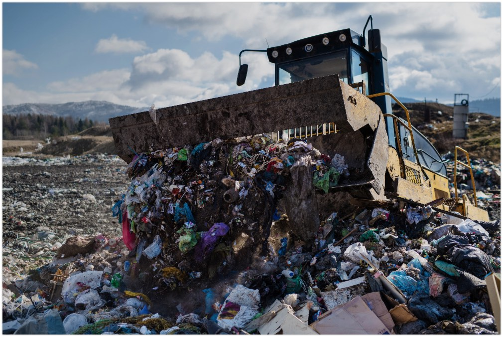 Garbage truck unloading waste on landfill, environmental concept
