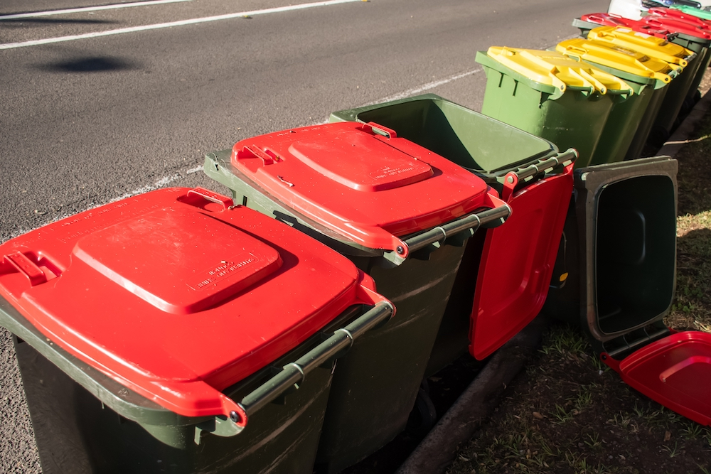 Australian garbage wheelie bins with colourful lids for general and green household waste lined up on the street kerbside for rubbish collection