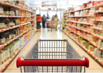 Shopping trolley, empty, with red handle on blur supermarket aisle background
