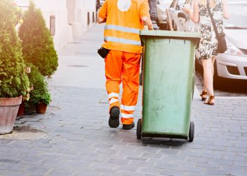Worker of cleaning company in orange uniform with a green garbage bin